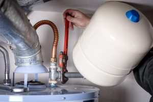 Plumbers does maintenance on a hot water heater