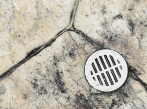 Wet outdoor tile floor drain hole close up
