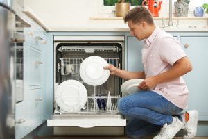 Man Loading Dishwasher In Kitchen