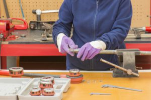 fontanero mide la rosca de la tuberia con el calibrador, herramientas sobre la mesa de trabajo
